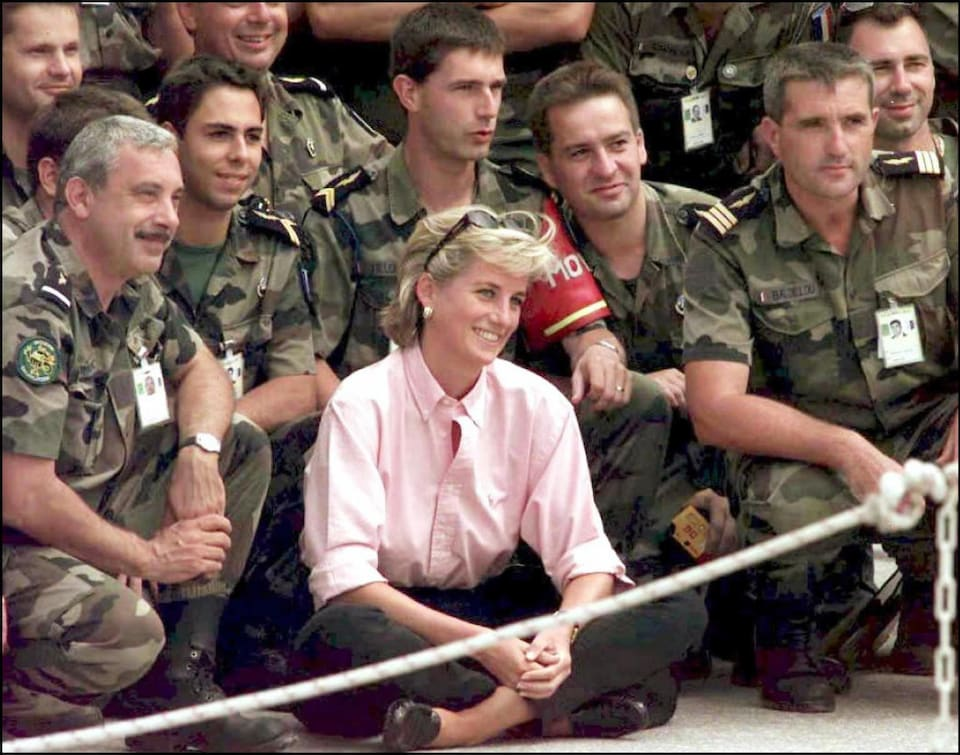 La princesse souriante en compagnie de soldats français à l'aéroport de Sarajevo en août 1997.