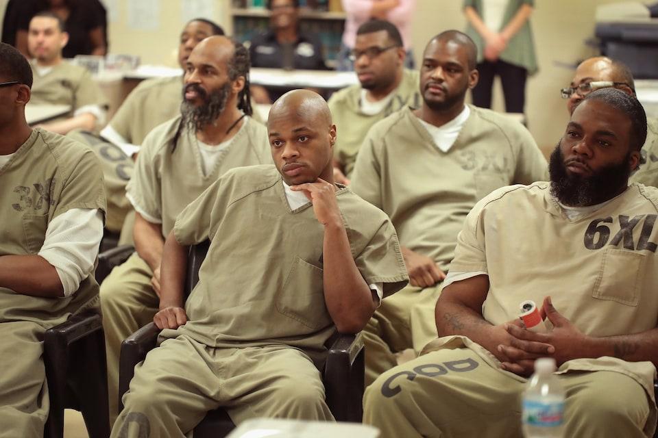 Une dizaine d'hommes noirs en tenue de prisonniers regardent devant eux.