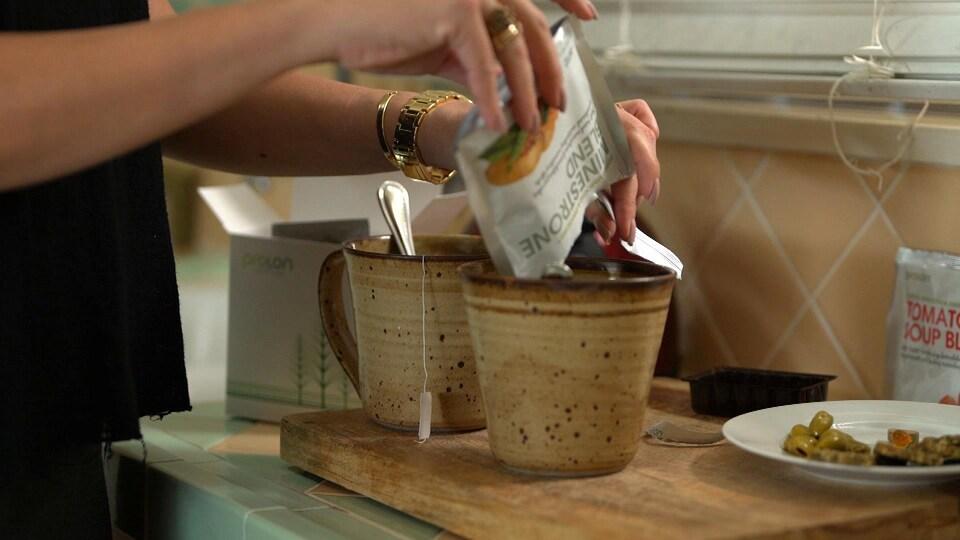 Gros plan sur les mains d'une femme qui verse le contenu d'un sachet dans une tasse posée sur un comptoir.