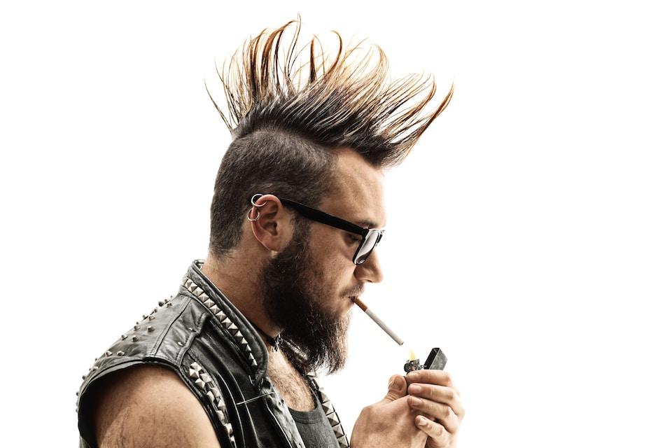 Photo d'un homme aux allures «punk» qui fume une cigarette.