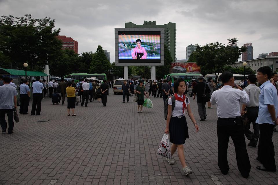 Des Nord-Coréens regardent un écran de télévision montrant une lectrice de nouvelles. D'autres résidents de la capitale vaquent à leurs occupations.
