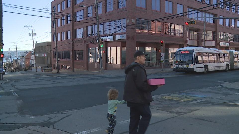 Un homme marche dans une rue du North End d'Haifax en tenant sa petite fille par la main.