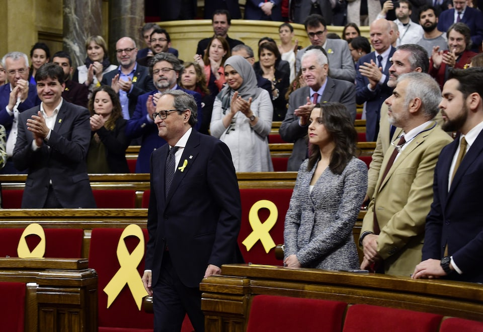 Quim Torra descend des marches pour se rendre à la tribune au Parlement catalan.