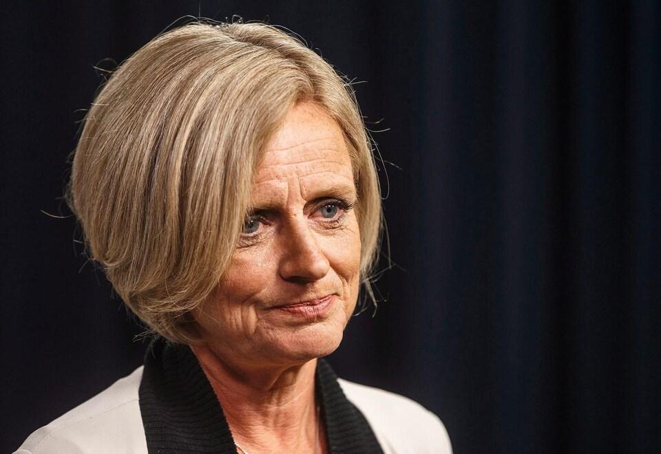 La première ministre écoute avec attention la question d'un journaliste lors d'une conférence de presse.