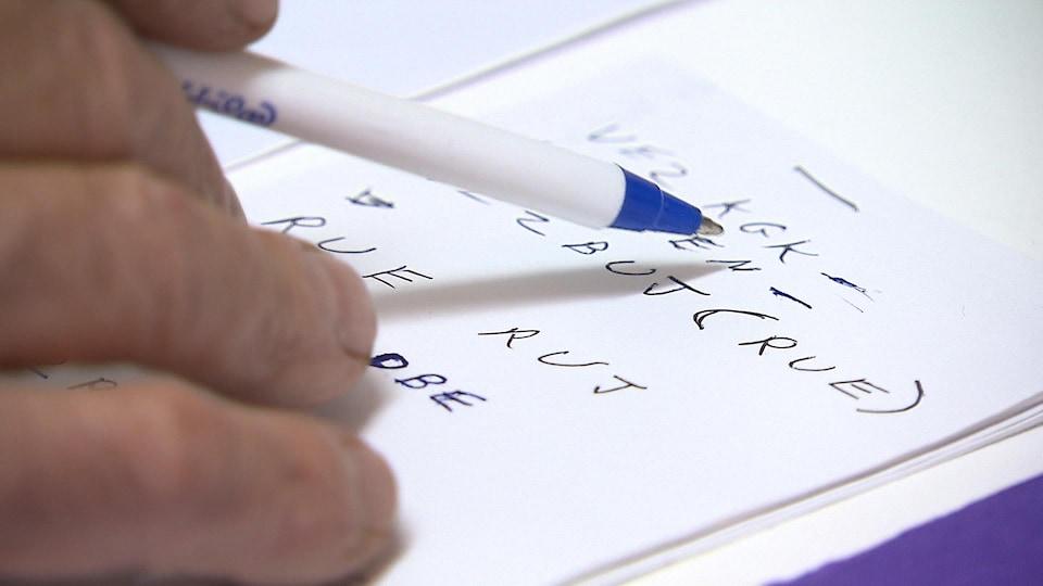 Des codes notés sur un morceau de papier. Une main qui écrit.