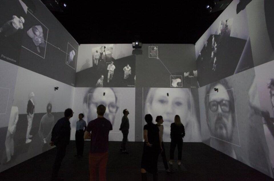 Des personnes regardent des images d'eux-mêmes sur un mur.
