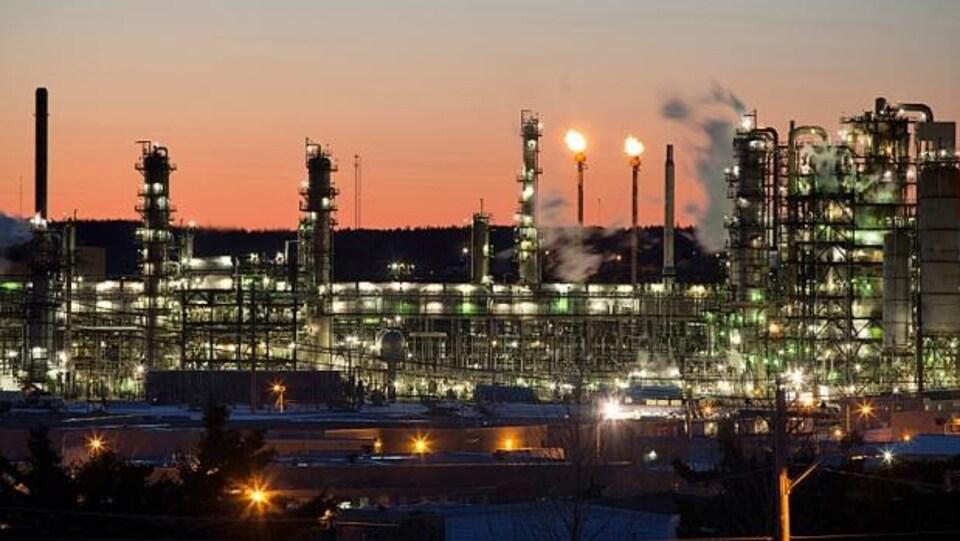 Les lumières et la fumée émanant des tours de la raffinerie
