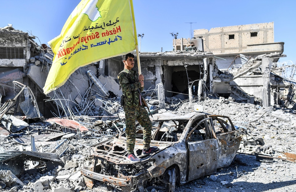 Un homme en uniforme militaire sur une carcasse de voiture brûlée tient un drapeau des FDS.