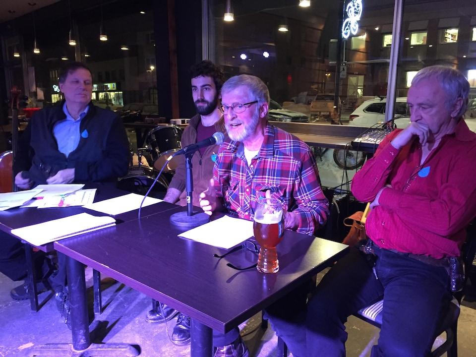 Un homme parle au micro, trois autres hommes à ses côtés derrière une table.