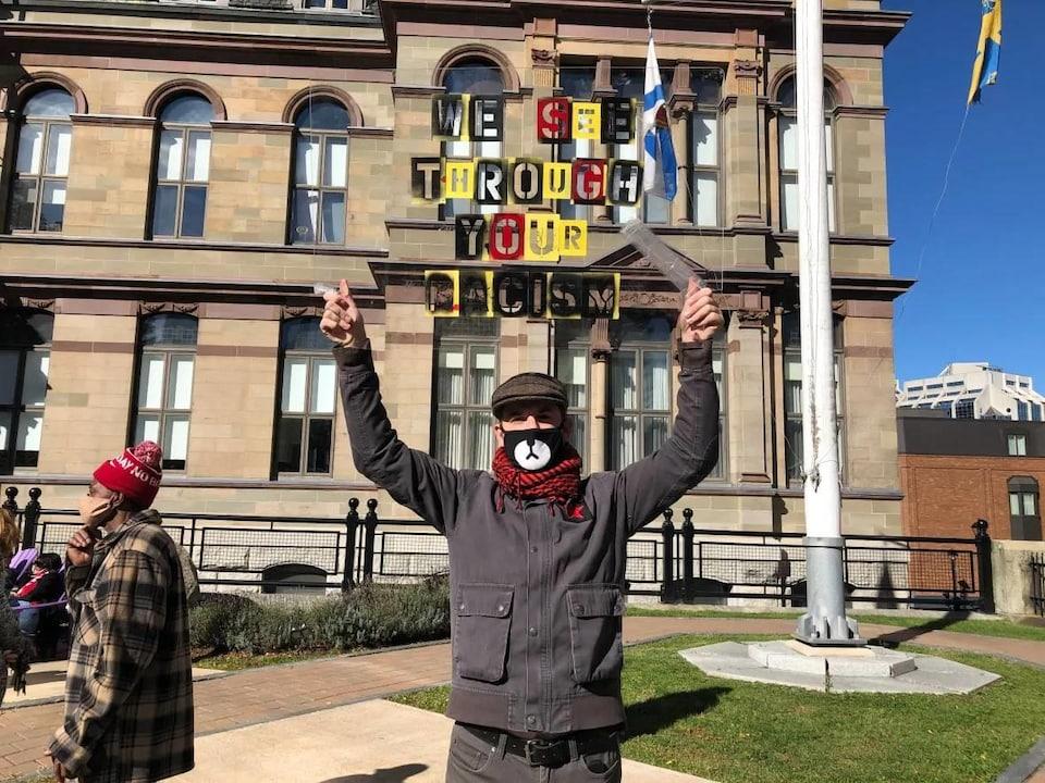 Un homme tient un écriteau transparent sur lequel est apposé le message « We see through your racism ».