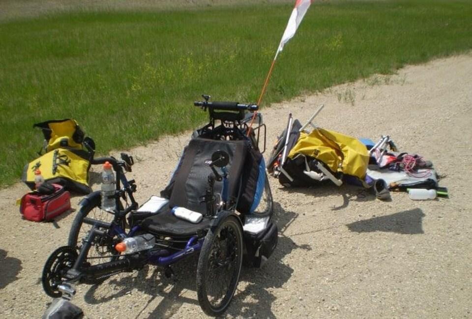 Le contenu de la remorque d'un vélo couché répandu sur la route après un accident.