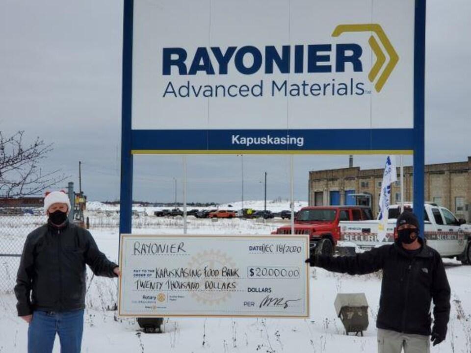 Deux employés de Rayonier tiennent un chèque géant de 20 000 dollars destiné à la banque alimentaire de Kapuskasing.