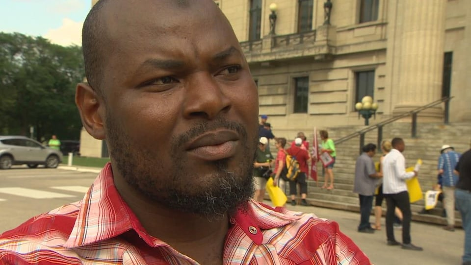 Gros plan du visage d'un homme de couleur noire qui a l'air sérieux.