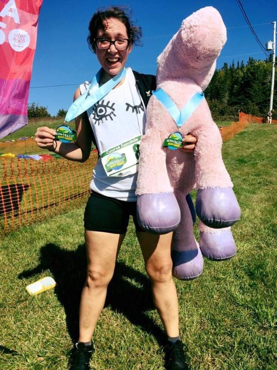 Rebecca Diaz affiche un grand sourire en montrant sa médaille de l'Ultratrail du bout du monde et une licorne en peluche.