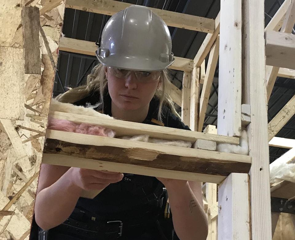 Rebecca Lemieux, élève en menuiserie-charpenterie isole un mur.