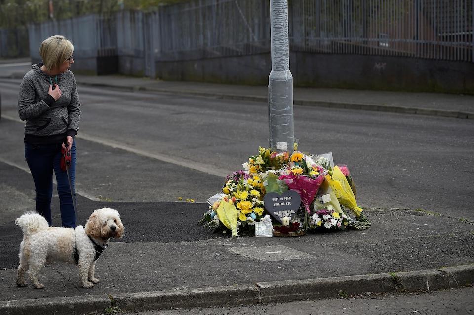 Une femme blonde d'âge moyen et son chien de type bichon observe les gerbes de fleurs posées au pied d'un poteau.