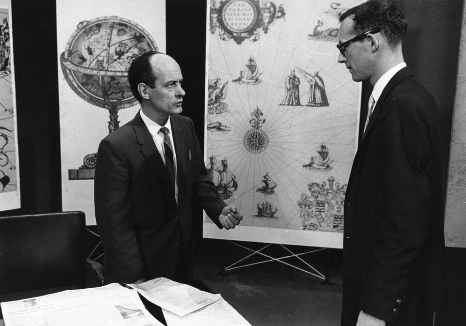 Sur le plateau, l'animateur René Lévesque discute avec le réalisateur Claude Sylvestre.
