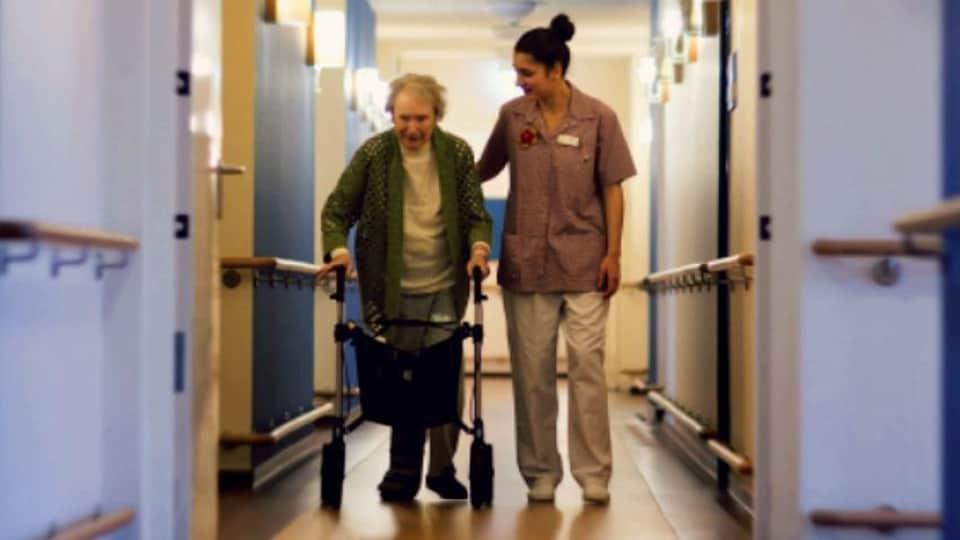 Une préposée aux soins aide une aînée à se déplacer dans un corridor.