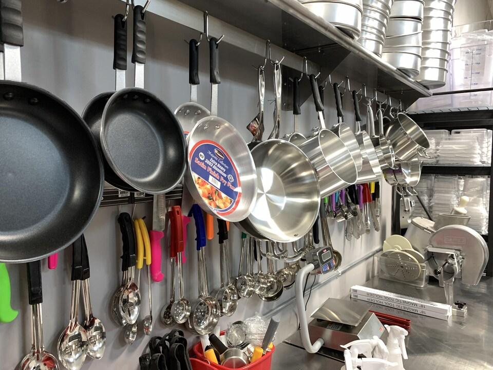 Des poêles à frire, des casseroles et des cuillères de toutes tailles accrochées à un mur.