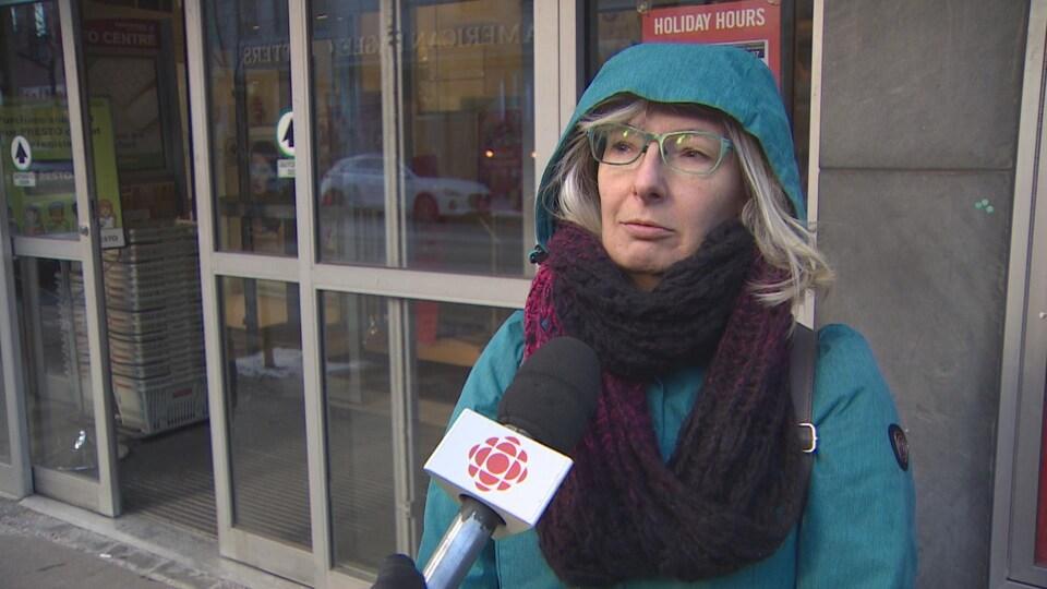 Une femme habillée d'un manteau bleu devant une boutique au centre-ville de Toronto.