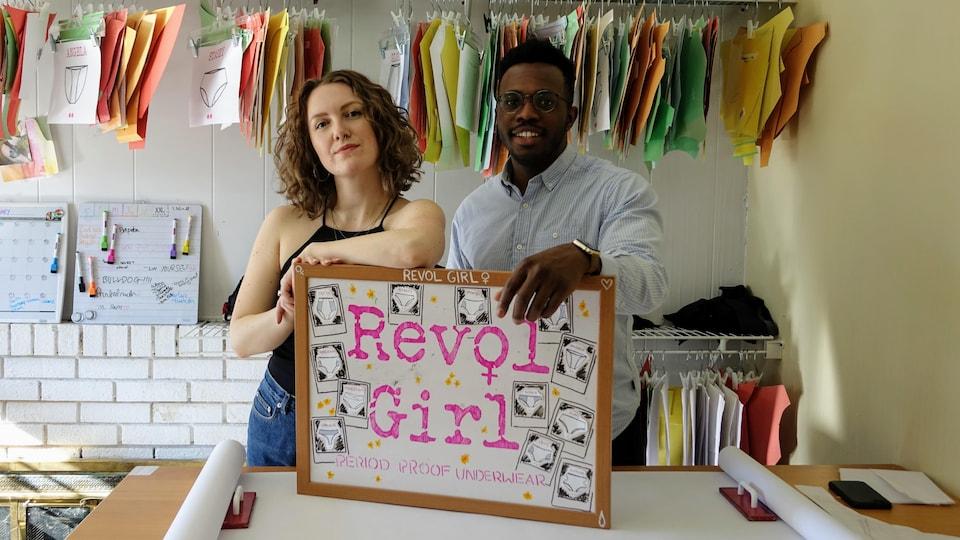 Sara et Mayo debout dans l'atelier tenant une affiche indiquant le nom de l'entreprise.