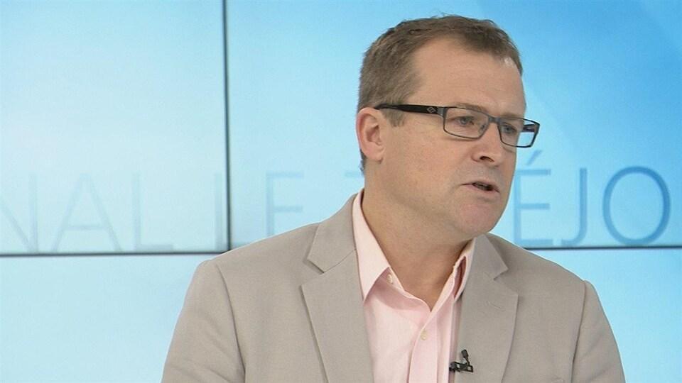 Richard Saillant porte des lunettes de vue. Un veston avec chemise. Il est en entrevue dans un studio de télévision