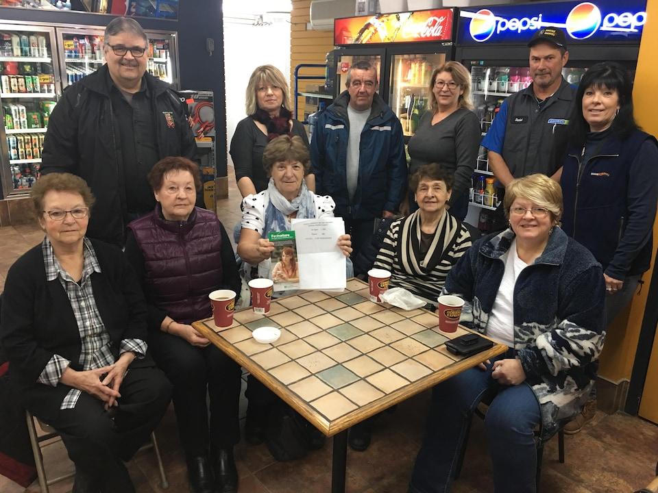 Dix citoyens et le maire de Ripon autour d'une table dans un commerce. L'un deux tient des brochures de la  caisse Desjardins.