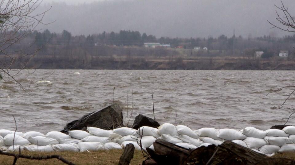Une petite muraille de sacs protège un terrain d'une rivière agitée.