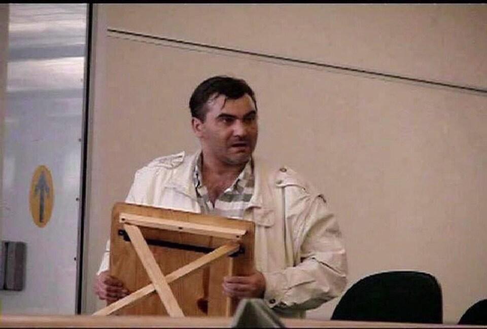 Robert Dziekanski brandit un meuble ressemblant à une petite table ou à un tabouret.