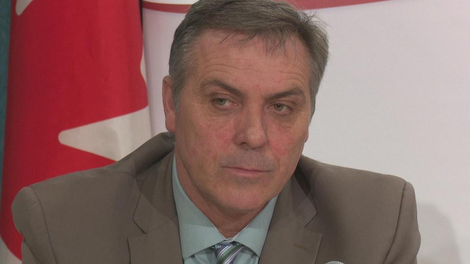 Robert Mitchell devant un drapeau du Canada.