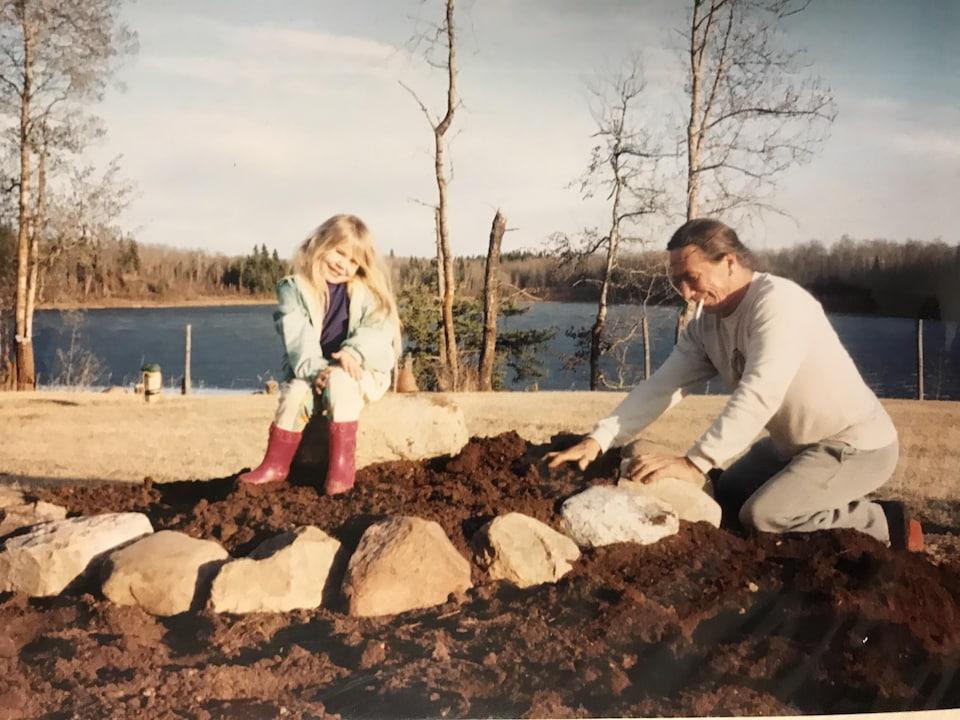 Un homme et sa fille devant un tas de terre et de roches.