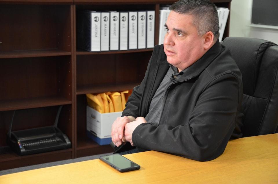 Un homme est assis dans son bureau et regarde vers la gauche.