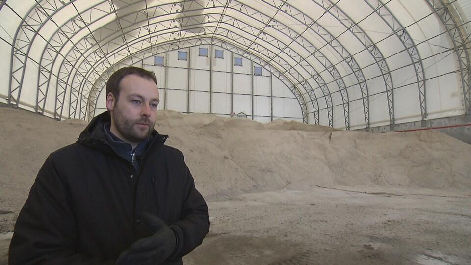 On voit M. Robitaille qui parle à la caméra. Il est devant un dépôt de sel de déglaçage.