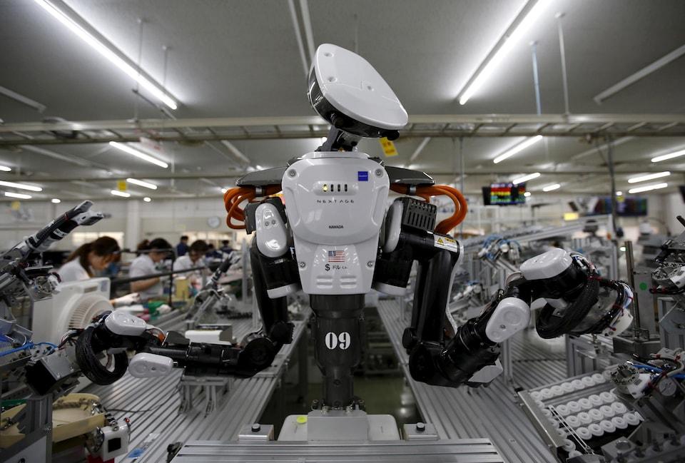 Un robot doté de deux bras et de ce qui ressemble à une tête, dans une manufacture.