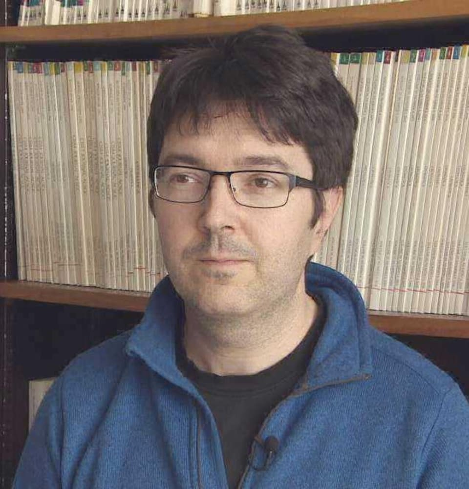 Rodolphe Devillers devant une bibliothèque.
