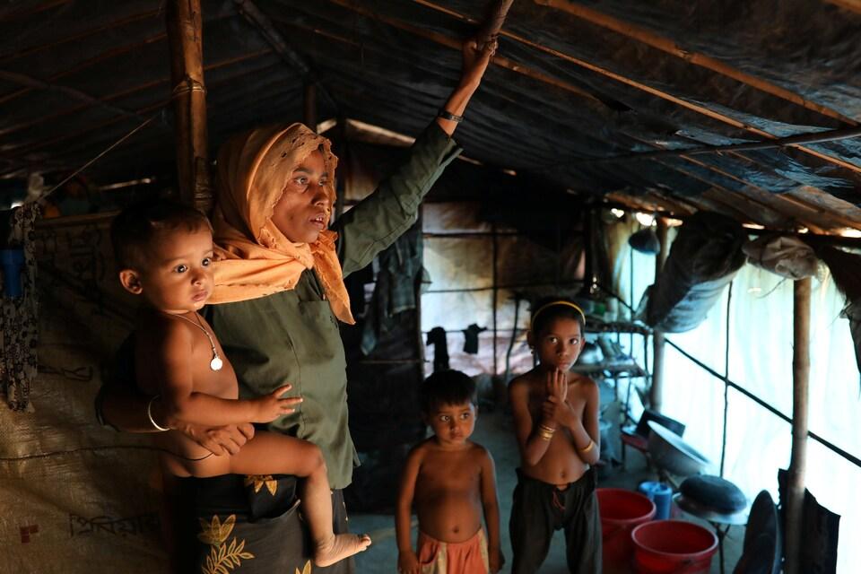 Une femme accompagnée de deux enfants tient un autre enfant dans ses bras, dans un abri de fortune.