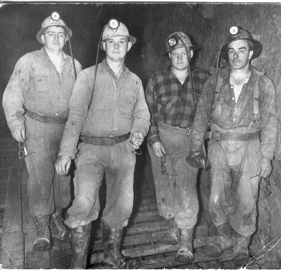 Une photo d'archives en noir et blanc montre des mineurs sous terre.