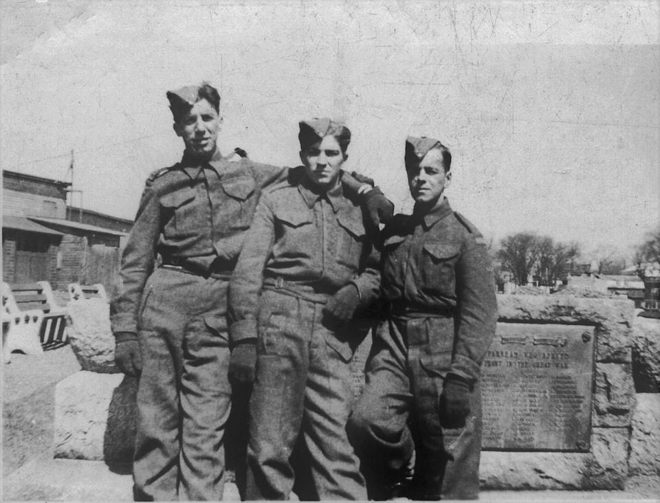 Une photo d'archives en noir et blanc montre trois soldats bras dessus, bras dessous.