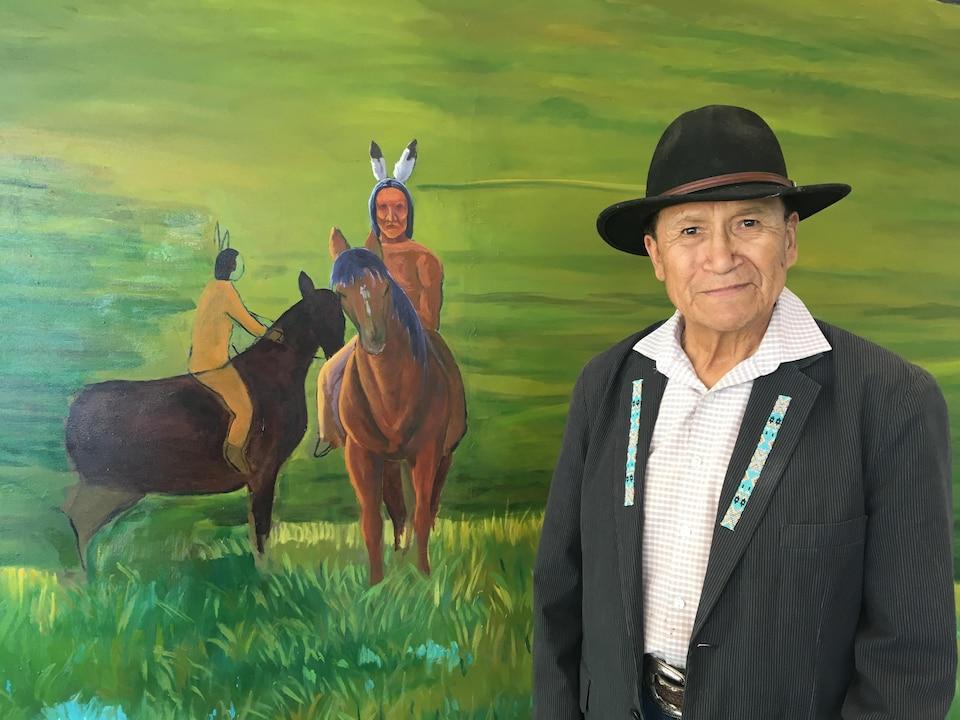 Roland Rollinmud pose devant une portion de son oeuvre représentant des cavaliers autochtones à cheval.