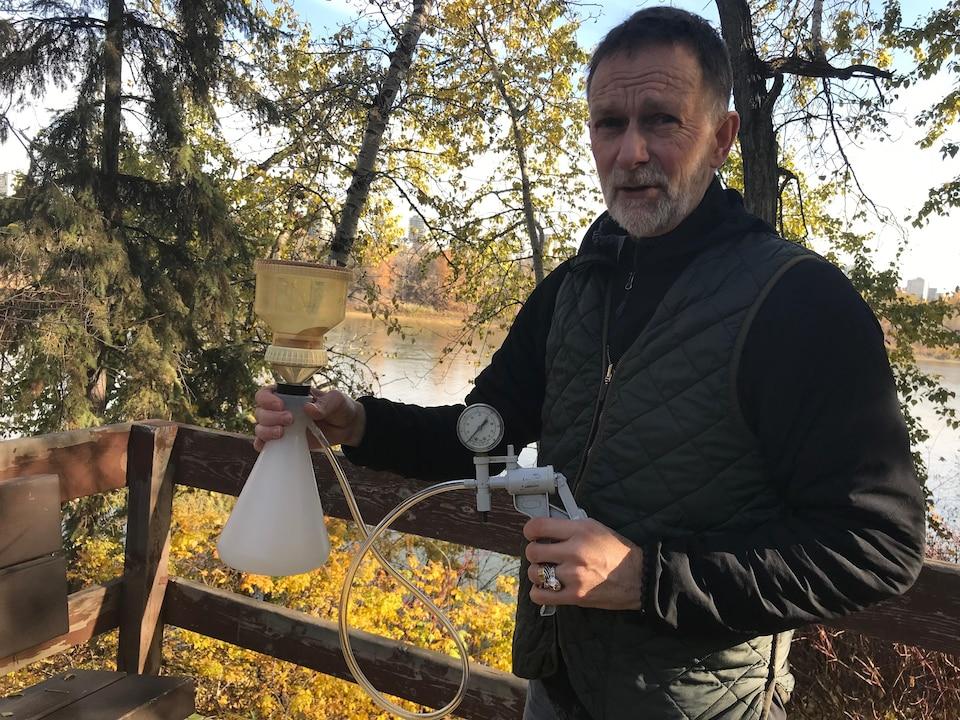 Un homme tient dans ses mains un dispositif de pompage et de filtrage d'eau aux abords de la rivière Saskatchewan Nord.