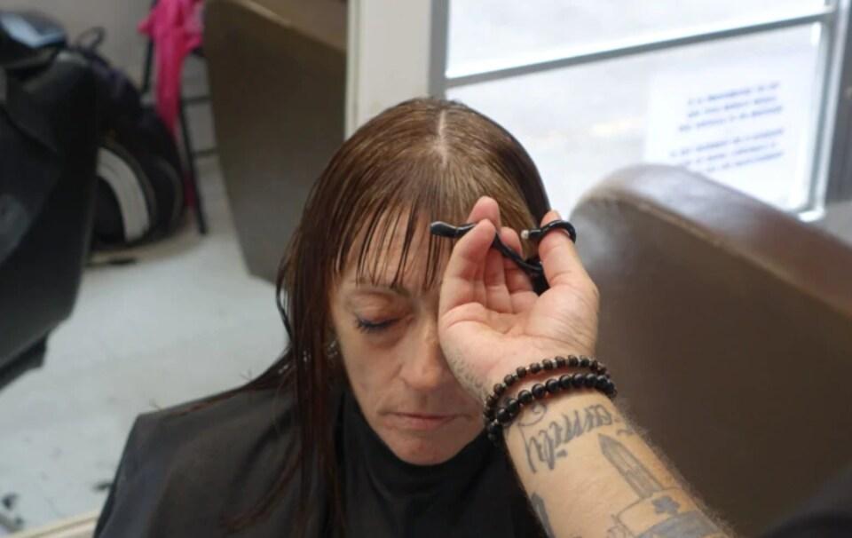 Une femme se fait couper les cheveux, de face, les yeux fermés.
