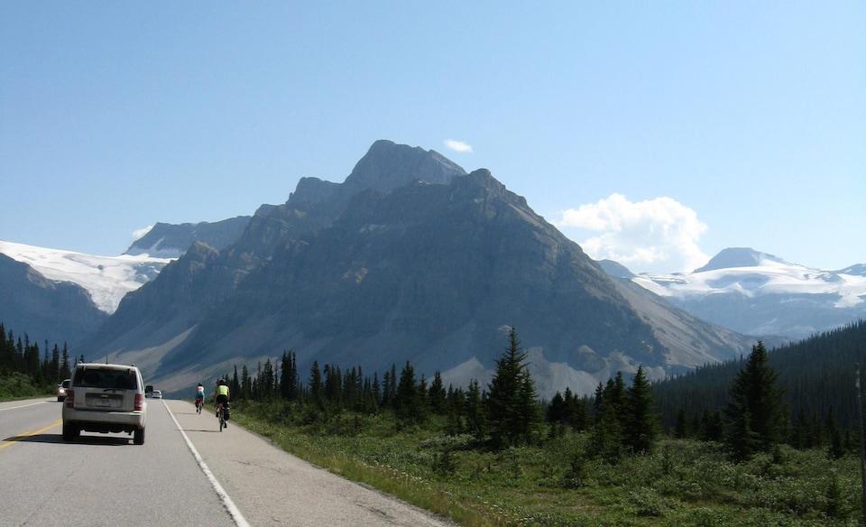Des voitures et des cyclistes sur une route au milieu des montagnes