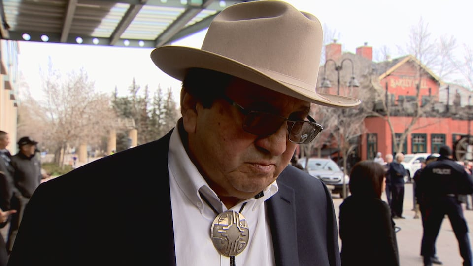 Roy Fox, avec des lunettes de soleil et un chapeau sur la tete, répond aux questions du journaliste
