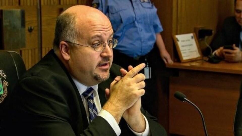Un homme à lunettes devant un microphone.