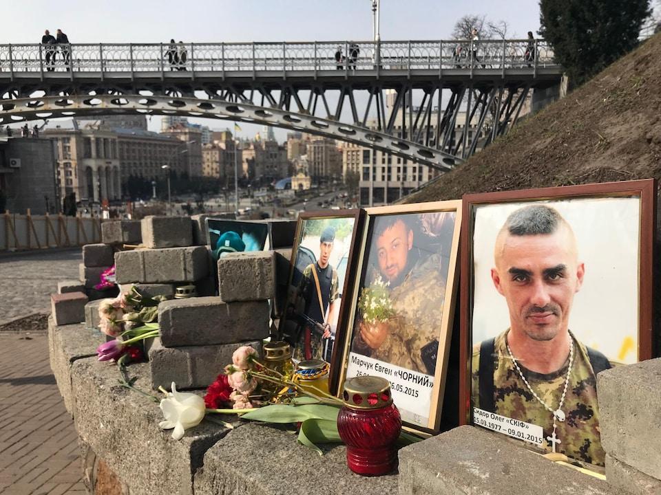 Des photographies et des chandelles sur un mur de brique, près d'un pont.