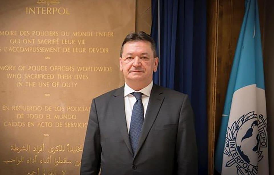 Alexandre Prokoptchuk devant un drapeau d'Interpol.