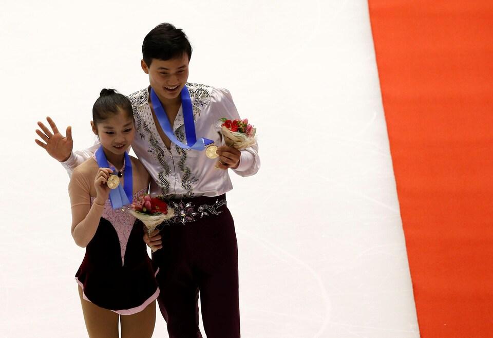 Ryom Tae-ok et Kim Ju-sik saluent la foule, médaille au cou, lors de leur qualification.