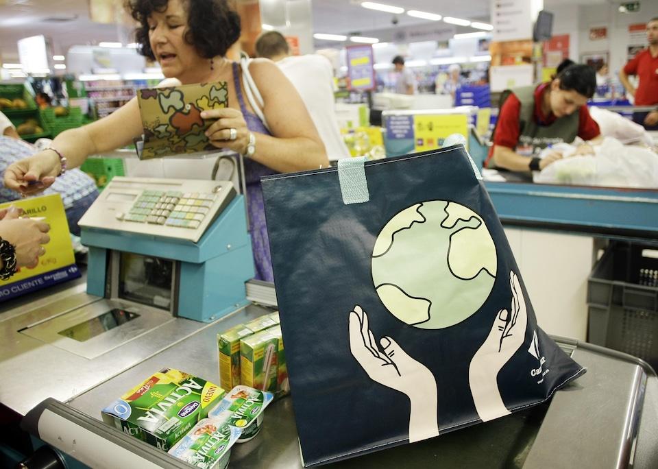 Une dame utilise un sac en plastique réutilisable sur lequel on peut voir la Terre tenue par deux mains.