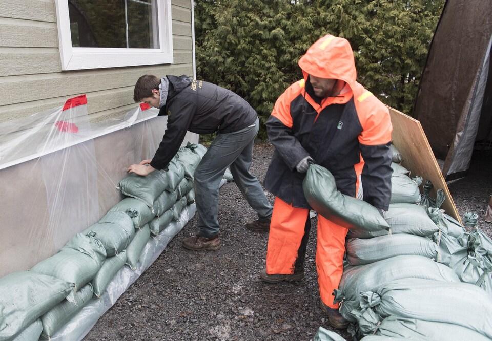 Deux hommes placent des sacs de sable près des fondations d'une maison.