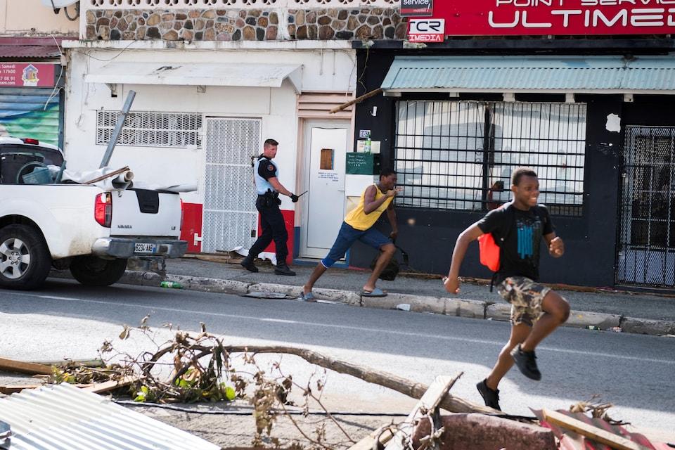 Un soldat de la gendarmerie française chasse deux jeunes pilleurs près de Marigot, sur l'île de Saint-Martin.